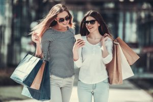 two girls with shopping bags looking at phone